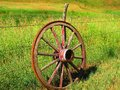 Wagon wheel a picture a leaning on a fence post Royalty Free Stock Image