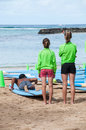 Waikiki surf lessons students observe native hawaiian instructor teach the way of the surfboard on beach hawaii Royalty Free Stock Photo