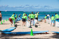Waikiki surf lessons students observe native hawaiian instructor teach the way of the surfboard on beach hawaii Stock Photo