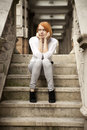 Wait attractive rad haired lady sitting on stairs of old building Royalty Free Stock Photo
