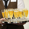 Waiter carrying a tray of champagne closeup view the hands in tall elegant flutes at wedding reception or catered event Stock Images