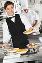 Waiter holding pasta dish happy with chef in background Stock Photography