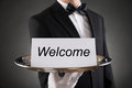 stock image of  Waiter Holding Plate With Welcome Text On Paper