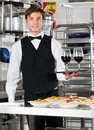 Waiter holding wineglasses on tray portrait of young in with pasta dishes commercial kitchen counter Stock Image