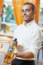 Waiter man in restaurant male sommelier steward sugesting wine bottle Stock Image