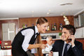 Waiter offering coffee to business man a pot of men in hotel café Royalty Free Stock Image