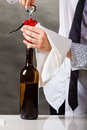 Waiter opens wine bottle. Royalty Free Stock Photo