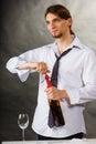 Waiter opens wine bottle.