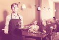 Waiter posing at table customers Royalty Free Stock Photo