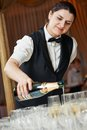 Waiter pour a glass of champagne female waitress during catering service at party Stock Images