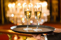 Waiter served champagne glasses on tray in restaurant a a fine dining a large chandelier is background Royalty Free Stock Images