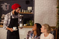 Waiter serving coffee and interacting with customers Royalty Free Stock Photo