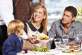 Waiter serving family in restaurant a a and bringing a full plate Royalty Free Stock Images