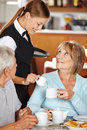 Waiter serving milk to coffee senior women in shop Royalty Free Stock Photos