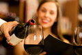 Waiter serving red wine to beautiful woman restaurant Royalty Free Stock Images