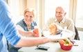 Waiter serving retired senior couple eating at vegan restaurant Royalty Free Stock Photo