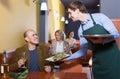 Waiter serving senior male customer in cafe