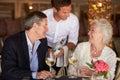 Waiter Serving Wine To Senior Couple In Restaurant