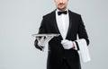 Waiter in tuxedo holding metal empty tray and napkin Royalty Free Stock Photo
