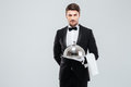 Waiter in tuxedo holding serving tray with cloche and napkin Royalty Free Stock Photo