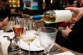 Waiting is pouring white wine in restaurant Stock Photo