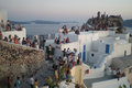Waiting for the sunset atmospheric blurry image of unrecognizable tourists watching and photographing famous of oia on santorini Stock Images