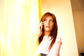 Waiting for you a beautiful woman at the window while talking on the phone Stock Photography