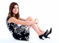 Waiting for you portrait of an attractive young woman on a white isolated background sitting with hands on legs Royalty Free Stock Photography