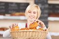 Waitress arranging breads in basket at cafe young Stock Image