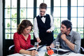 Waitress assisting a couple while selecting menu Royalty Free Stock Photo