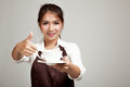 Waitress or barista  in apron thumbs up  holding coffee Royalty Free Stock Photo