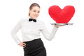 A waitress with bow tie holding a tray with red heart on it tray Royalty Free Stock Photos