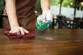Waitress cleaning the table with spray disinfectant Royalty Free Stock Photo
