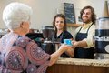 Waitress with colleague serving coffee to woman at mid adult senior women counter in cafe Royalty Free Stock Photos