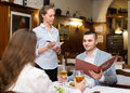 Waitress and guests in cafe Royalty Free Stock Photo