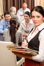 Waitress hold menu business people at restaurant Stock Image
