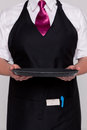 Waitress holding an empty tray a wearing apron and tie good image for product placement Stock Images