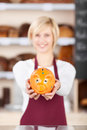 Waitress holding piggybank at bakery counter portrait of young in Stock Photo