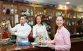 Waitress holding tray with glasses bartenders at the distance Stock Photography