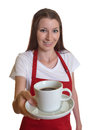 Waitress with long brunette hair offering fresh coffee laughing has a cup of hot in her hand on a white background Stock Images