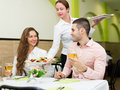 Waitress serving food to visitors charming meal table Royalty Free Stock Image