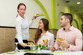 Waitress serving food to visitors positive brings plate with prepared table Stock Image