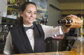 Waitress serving red wine young in glass Stock Image