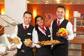 Waitress and waiters posing with food at buffet in a restaurant Royalty Free Stock Photo