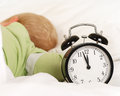 Wake up with alarm clock little caucasian boy during daytime sleep Stock Photography