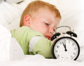 Wake up with alarm clock little caucasian boy during daytime sleep Stock Image