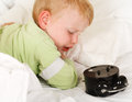 Wake up with alarm clock little caucasian boy in the morning Royalty Free Stock Photos