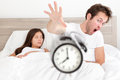 Wake up couple waking up early throwing alarm clock funny bed concept with young interracial late man Royalty Free Stock Photo