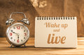 wake up and live text on notebook with alarm clock on wood table Royalty Free Stock Photo