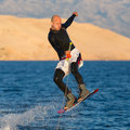Wakeboarder in sunset wetsuit jumping wakeboarding is a surface water sport which involves riding a wakeboard over the surface Stock Image